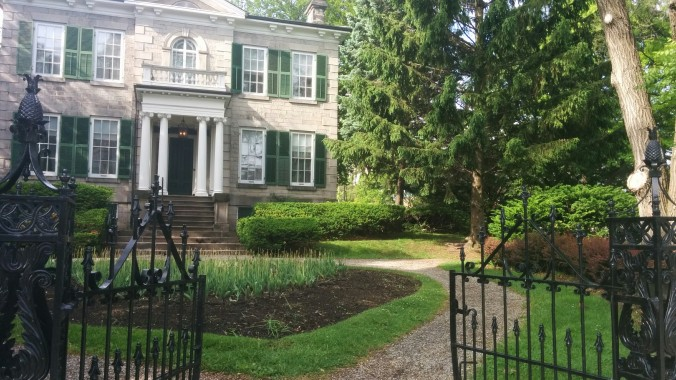 At the front. The gates stand open and the mansion sits there, in all its glory.